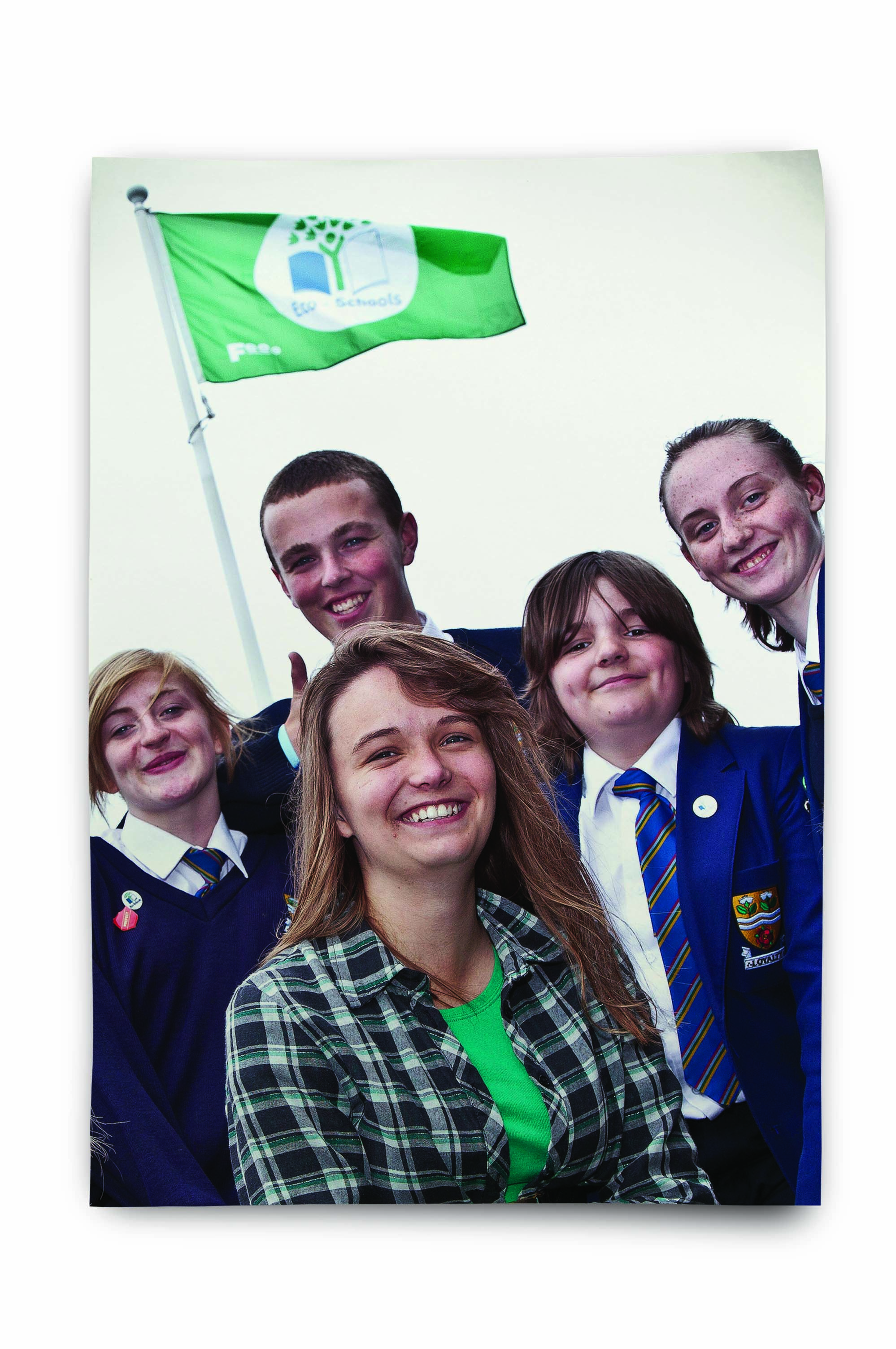 An image of a teacher and school children in front of an Eco-Schools flag
