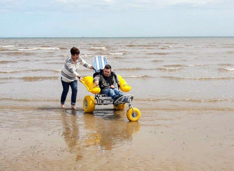 An image of a gentleman using a beach wheelchair