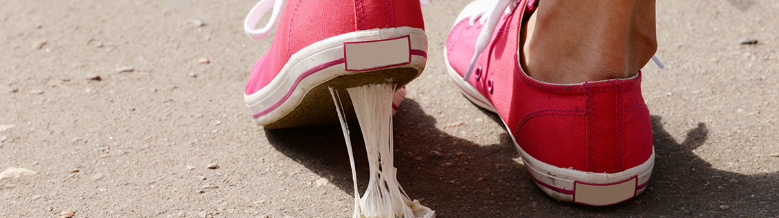 An image of pink trainers stepping in chewing gum