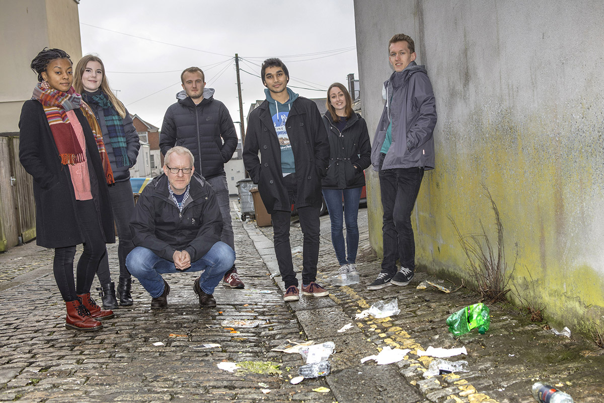 An image of university students standing outside surrounded by litter