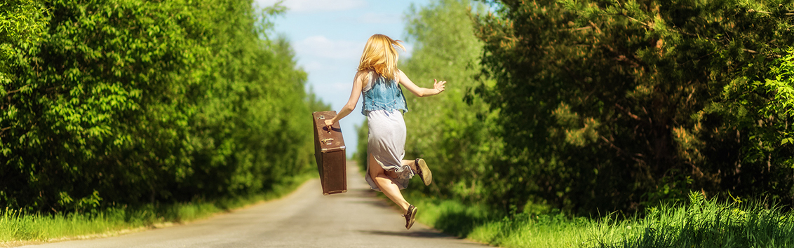 An image of a girl jumping in the middle of country road with a suitcase