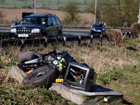 An image of fly tipping and a car driving past it
